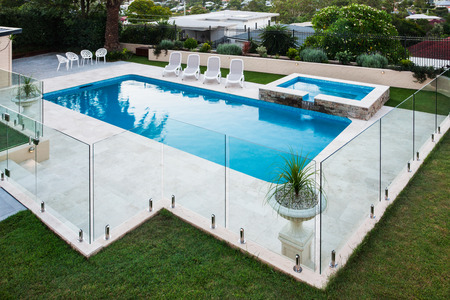 Modern swimming pool covered with glass panels beside a green lawn garden including trees and chairs Editorial