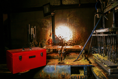 old metal: Dirty old workshop in a dark room with metal machines and red suitcase on the steel work top