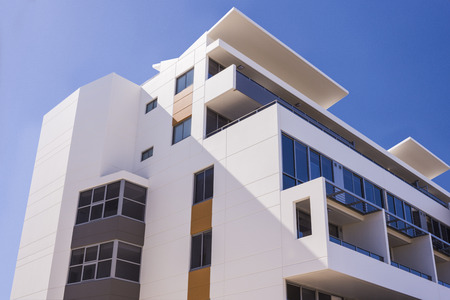 showed: Modern building with blue sky showed the upper part with white walls and windows around Stock Photo