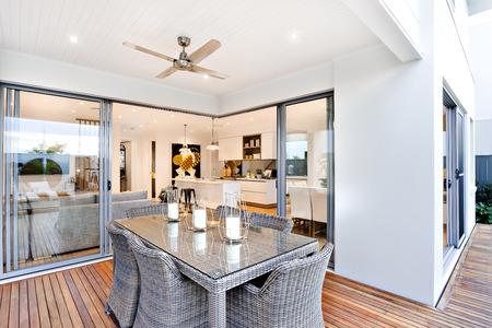 patio al aire libre con mesa estableció al lado de una entrada al interior de una casa moderna con una cocina, hay velas en la mesa bajo el ventilador