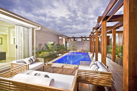 Wood decorated swimming pool area with green plants and glass panel cover  under the cloudy sky in a modern house or hotel Stock Photo