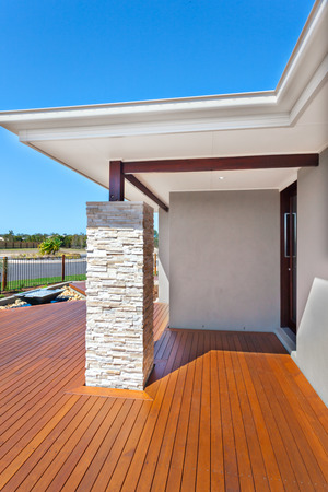 Luxury house with a blue sky background without clouds in behind, There are rectangle shaped long wooden bars vertically fixed to the floor. The ceiling and the roof are held by a brown color wooden beams and a huge pillar that made in stone granite piece