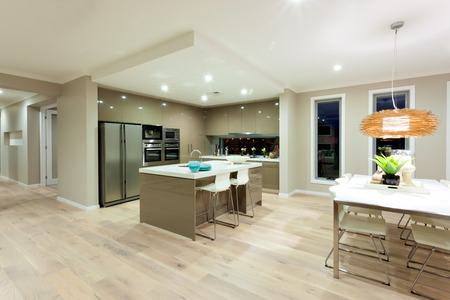 ceiling plate: Dinning area has a white table and chairs with hanging lamp covered with bamboo or rattan decorative nest over the ornamental items on the table. The kitchen is next to the table with white ceramic counter top and huge wall cabinets and pantry cupboards a