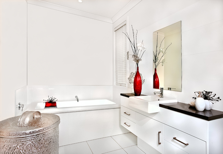 washstand: Washroom walls are white with same color bath tub and washstand. There are drawers under the sink. The mirror is fixed to the wall behind the sink and a closed window besides the water tub. Stock Photo