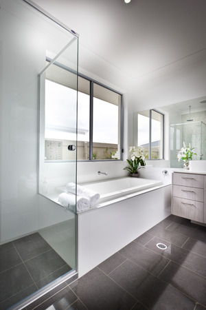 towels wall: Luxury bathroom floor is made of shiny tiles. The bathing area is covered with glass panels that next to the white ceramic bath tub under the window. There are few towels against the mirror on the white wall
