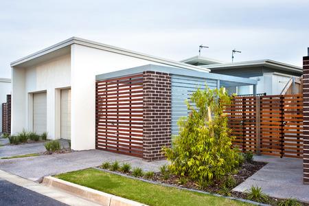 anverso casa de lujo con la puerta de madera y jardín, el árbol de fantasía de color verde cultivado al lado del césped cerca de la puerta de madera con paredes de ladrillo en un día soleado Foto de archivo
