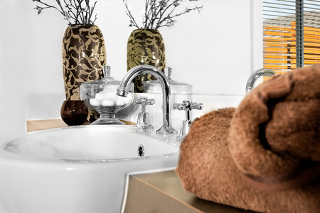 washstand: Modern silver color washstand is curved and fixed to the white ceramic sink. The brown wool towel is blurred on the counter front of the mirror. There is a dark colored glass next to the fancy vase and glass bowl including Cotton balls
