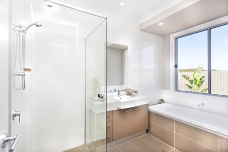 washstand: Bathroom of a luxurious house with bathing area from the left side surround by glasses and a silver faucet with white washstand in front of a vertical rectangle shaped mirror, there is an ornamental plant inside of a tall glass vase from the left and a fi
