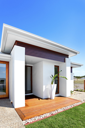 lath in modern: Outdoor of a modern house with green lawn, front view from the left side of the house, there is a wooden floor and plant with a tall vase of the entrance. There are two major concrete pillars holding the front roof, The ceiling has wooden lath as a popula Stock Photo