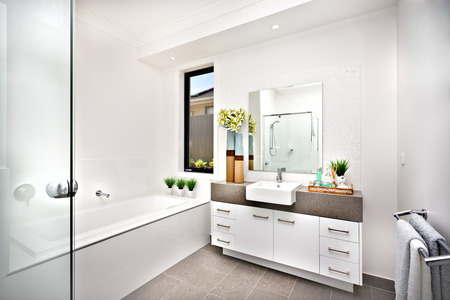 Washroom with a bath tub beside a window and tap, the room isdecorated nicely with green plants on vase beside the basin and tap near  the counter cupboard