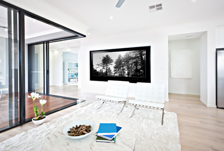 tv panel: Luxury living room and glass door entrance to inside with white walls and black tv panel shows the natural tress, the round table with books on the wool carpet on the floor