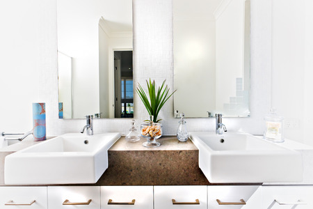 Counter top of a washroom including sink and taps beside the green plant near a herbal and soap reflection on the mirror
