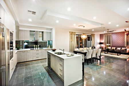 illuminate: Modern and shiny kitchen with dining and living area, including a counter top and kitchenware on the reflective tiles, there are lights flashing at night