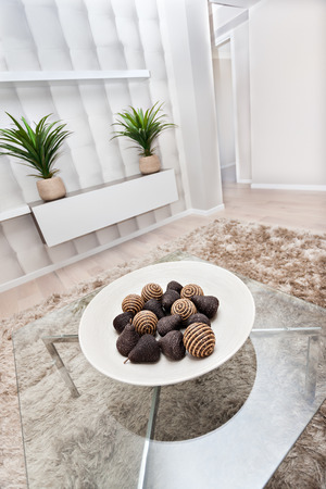 decorative item: Fruit shaped brown color wool yarn ball or a decorative item made by a brown thread spun around a stick and a ball shaped item made of bamboo or reed can be seen on a white plate, dish is in the middle of glass tables and there is a fur carpet on the floo Stock Photo