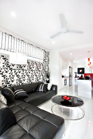 better living: Close up of a black sofa with pillows near round table like a drum. The wall have better look with vines art pasting next to the flashing white lamp. The hallway starts from living room with a fan