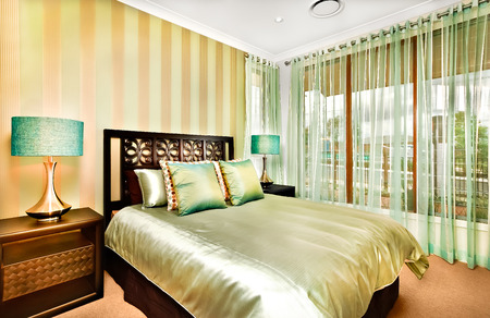king size bed: There is a huge king size bed made of wood in a modern room with shiny pillows and sheets on it, Glossy brass looking cupboards with shiny table lamps on it. Windows with curtains show the outside