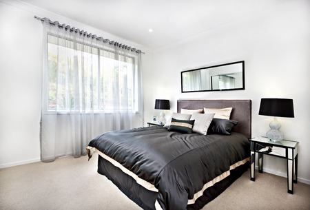 decoracion mesas: Modern bedroom with black decoration and mirror beside lamps including blanket and pillows beside the glass tables, there is a curtain covered the window with the sunlight spread