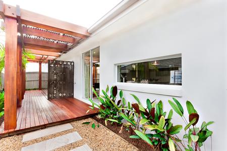 家の入口の正面には、バーは、木の床にアタッチされた梁の長いタイルと砂利生家、彫刻が施された木製の壁と柱の白い壁の近くの観葉植物の横に