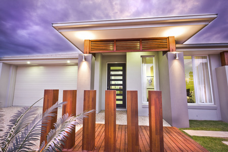 Modern mansion illuminated at night with purple sky beside the wooden floor and pillar garden in front of the garage and green grass lawn, there are light flashing  inside and outside of the house