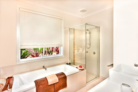 washstand: Luxury washroom prepared with towels and soap in the white color bath tub, bathing area covers with the glass room next to the water tub. A washstand from the right side