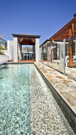 Modern Swimming Pool Side With Outside Patio Area And Wooden Pillars In A  Sunny Day With