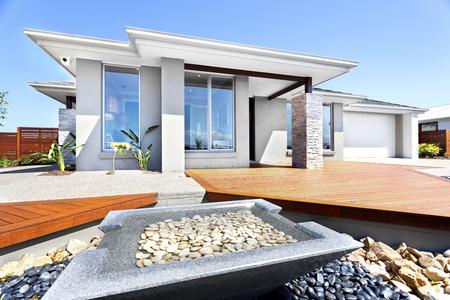 Patio y jardín bien decorados con elementos de piedra frente a una casa moderna, primer plano de un pequeño estanque de forma cuadrada hecho de piedra pura que incluye grava y agua en su interior. Hay rocas blancas y negras alrededor del estanque.