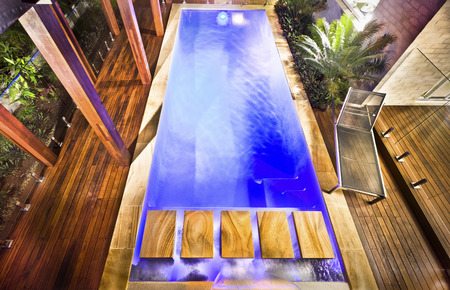 foot step: High view of the modern blue water swimming pool with wooden pillars and floor around as a pool side, there is a foot step bridge over the water