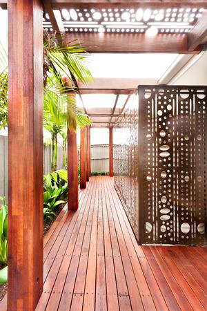 ファサード部廊下くださった木の床と総木製装飾屋外デザインと彫刻を施した大きな壁のような家の裏に沿って豪華な家が木の横にある柱します。