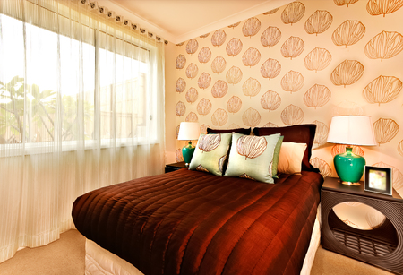 adentro y afuera: Luxury bed with huge brown color mattress and light blue pillows on it, there are small table that show the a circle Carve. There are two green table lamps made of ceramic. Outside can be seen through the window curtain Foto de archivo