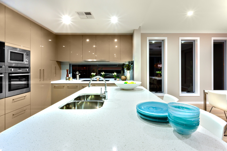Silver sink with faucet installed to counter top and blue and white dishes on it. The kitchen includes lots of wall cabinets and pantry cupboards. The oven is also fixed to the wall. Long glass windows on the wall and there are lights working Stock Photo