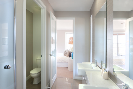 tap room: Closeup of a big mirrors on the wall near to the tap and white sink with liquid soap bottle, the toilet bowl isolated in a room. There is a way to the bedroom from the washroom and it should be attached to the bedroom and in a luxurious hotel or home, pil