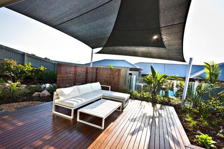 Outdoor patio met witte banken en houten vloer in een zonnige dag, die ook bedekt met een hut van het dak over de hekken en glazen panelen in de woonwijk