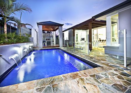 저녁에 하늘 아래 기와 풀 사이드와 어두운 푸른 물과 함께 유리 커버와 현대 수영장 측면 스톡 콘텐츠