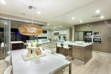 Inside of this house included with lots of small flashing lights under the ceiling. There is a lamp made in bamboo hanging over a white table. There are kitchen items and living room decorations next to it. White candles on the table