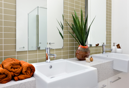 Modern washing area, including an orange color towel with silver faucet and white sink next to the natural fancy items in a luxury house or hotel