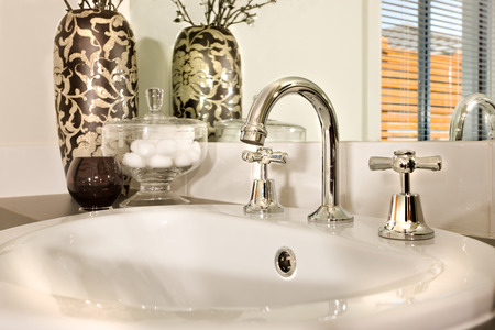 Modern sink and a faucet closeup view next to the glass with a vase decorated with vines beside to a glass bowl, The sink is shiny white made of ceramic and the tap is curved and made in silver steel and a mirror behind the countertop