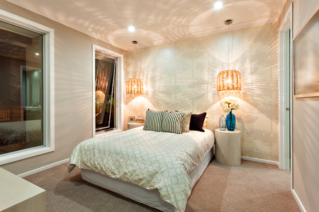 without windows: Modern bedroom walls beautifully illuminated with the pattern of a light that came through the bamboo or rattan lamps, the room has a huge bed with pillows and some flowers in the blue glass bottles on the table, there are two windows without curtains and Stock Photo