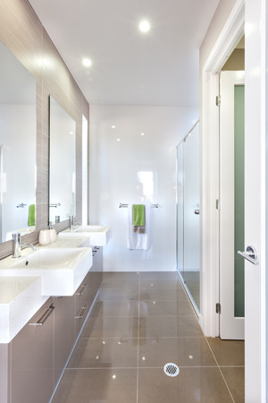 Modern Washroom is very shiny light brown color floor tiles with well illuminated walls with lights. The shower area attached to the white wall from the right side. There are towels hanging near it. The bathroom includes big mirrors and at least two moder