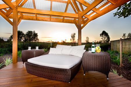 白いマットレスと枕、籐または類似の材料全て、日没では、2 つのテーブルが付いているベッド、場所製は木製の床、柱、屋根の木製の梁を保持して