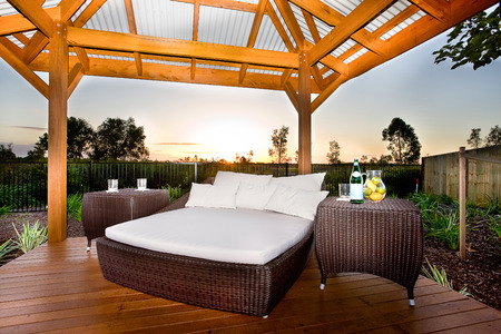 Place is made by wooden floor and pillars that holding a wooden beams in the roof, There is a bed with white mattress and pillows and two tables made in rattan or similar material, all prepared at the sundown