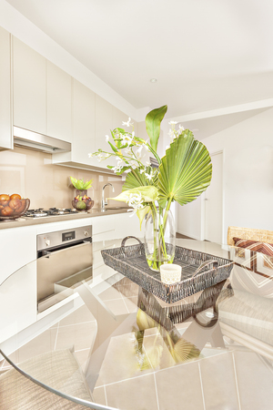 ceiling plate: Fresh flower pot on glass table near kitchen, oven and gas cooker have attached to the pantry cupboard, ceramics and fruits close to cookers, flowers and leaves are more colorful also attractive. Stock Photo