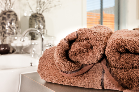 Towel has fur and very thick from the view, it is a dark brown color textile in a modern washroom, there is a sink with a faucet and some fancy items blurred in the background
