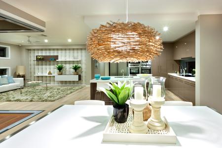 ランプカバーや竹や籐の材料で作られたフィルター。それは黒の光沢のある花瓶に緑の植物で白いテーブルと白の燭台で 2 つのキャンドルを照らし 写真素材