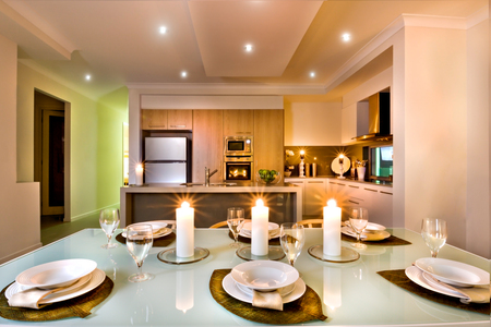 White plates are ready to serve in the dining area near to the kitchen, whole place lighted with white flashing candles, There are wine glasses and dishes on a leaf shaped braid.