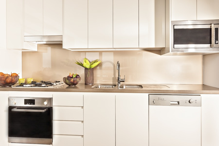 ceiling plate: Kitchen interior and tools illuminated with lights, oven and gas cooker have attached to the pantry cupboard, flower pot also fruits plate near the wash basin, perfect lightning. Stock Photo
