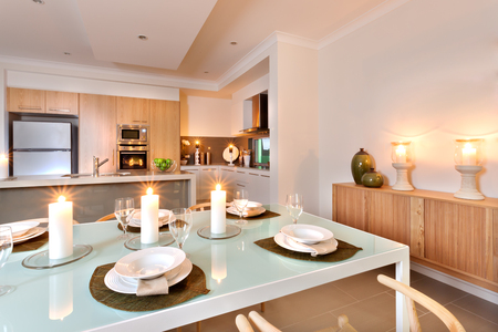 Modern kitchen area included a refrigerator and a wall oven decorated with flashing candles around the room, giving an extra shiny light to the room illumination. The table with empty white dishes and empty glasses ready to receive meals Stock Photo