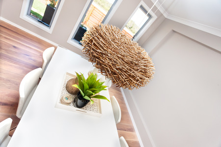 dried gourd: Interior decoration of a modern dining room focusing to the natural sources of adornment like bamboo nest hanging with lamp inside over the white table, there are six white chairs around the table and beautiful ornamental plant with shiny black vase on th Stock Photo