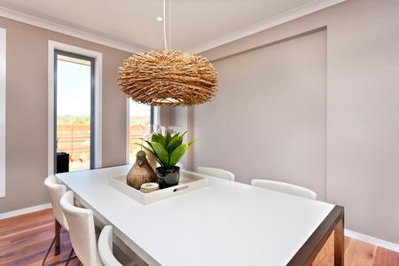 ダイニング テーブルと椅子、白い色と古典的な壁はグレー色で、窓周り白のカラー フレームがあります。竹・籐のテーブル、光としてこの木製の巣の作品の上にぶら下がってインテリア ランプがあります。 写真素材 - 67966895