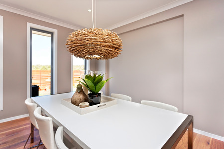 Dinning table and chairs are white color and classic, the walls are gray in color and there are white color frames around the windows. There is an interior decoration lamp made of bamboo or rattan hanging over the table, this wooden nest works as a light