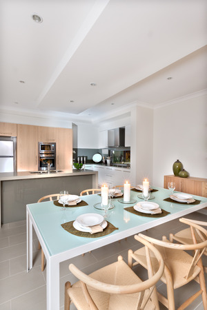 diningroom: There are three white candles flashing top of the light blue and shiny dining table surrounded by white dishes and wine glasses. Wooden chairs around the small table in front of the kitchen counter top with wall oven. The house ceiling is white and there